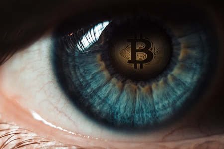 Bitcoin. Eye of a person with the bitcoin coin logo in the pupil Stock Photo