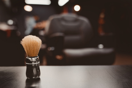 brush for shaving beard along with bowl, blurred background of hair salon for men, barber shop