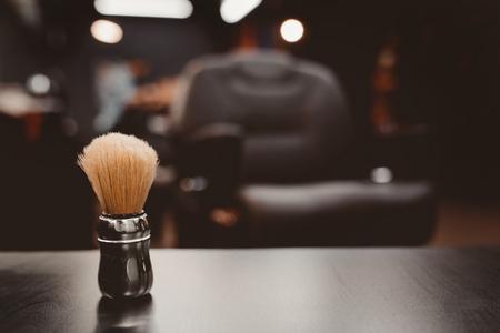 pędzel do golenia brody wraz z miską, rozmyte tło salonu fryzjerskiego dla mężczyzn, fryzjer