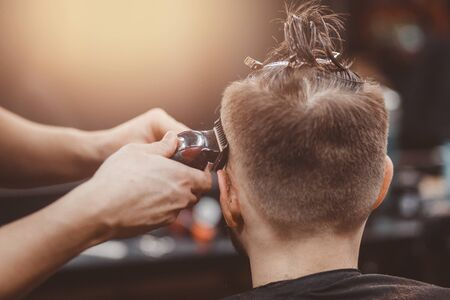 Barbershop. Barber shears client with hair machine.
