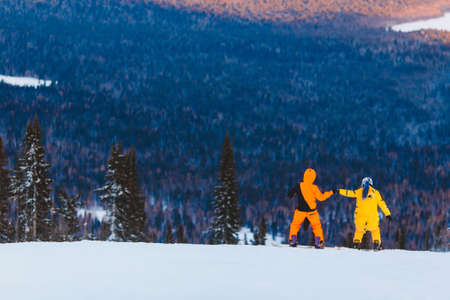 Loving couple on snowboards look mountain, sunset, concept of St. Valentine