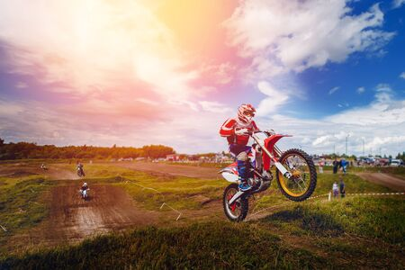 Racer on dirtbike motorcycle jumps and takes off over the track, in background the opponent is catching up. Concept primacy, rivalry, competition, extreme