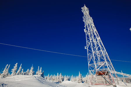 Cellular towers are icy with frost and cold, wires in the snow. abnormal frost, broken wires, winter Stock Photo