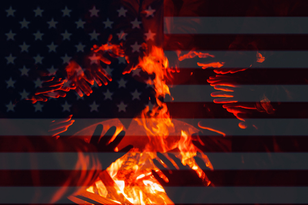 Refugees, illegal immigrants in America are warming their hands in fire of barrel fire. American flag