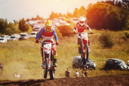 Racer op motorfiets neemt deel aan cross-country motorcross, springt en vertrekt op springplank tegen hemel. Concept actieve extreme rust.