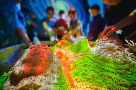 Children play with kinetic sand. Concept simulator of earth, volcanoes, relief and soil surface.
