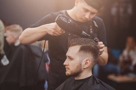 Barber shop. Master stacks hair of men hairdryer in barbershop, hairdresser makes hairstyle for young man