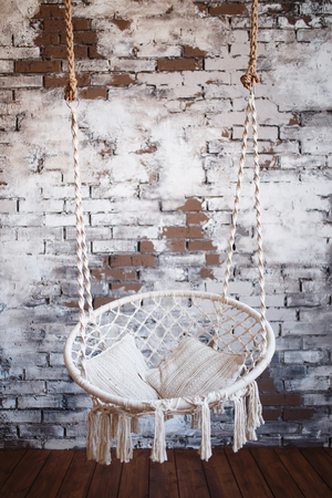 Armchair hanging. Design of a swing for the house from ropes and a rope with white pillows