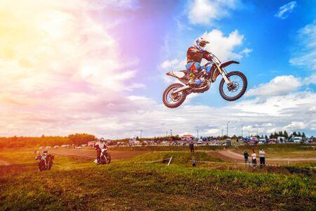 오토바이 경주 선수는 크로스 컨츄리 크로스 컨트리에 참가하고 점프하며 하늘을 나는 발판에서 벗어납니다. 개념 활성 극단적 인 나머지입니다.