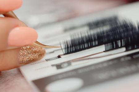 Eyelashes. Close-up tool for eyelash extension. Master of tweezers is working.
