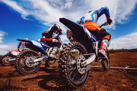 Team van atleten op mountainbikes start, rook en stof vliegen van onder de wielen in het hele land. Concept actieve rust motorcross.