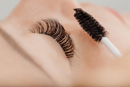 Eyelash extension procedure. Beautiful woman with long eyelashes in beauty spa salon.