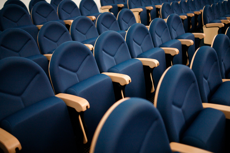 Seats are arranged in row in hall of opera, theater, cinema. Comfortable and soft chairs.