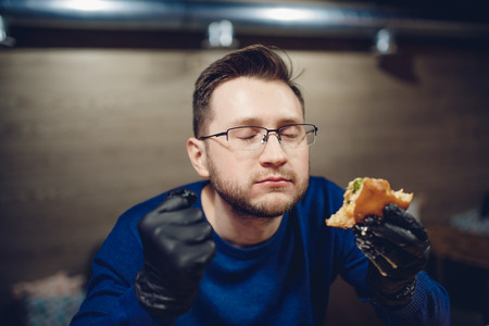Man Hands in black gloves wearing gloves is experiencing a nuisance from the burger.