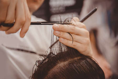 Barbershop. Close-up of man haircut, master does the hair styling in barber shop Stock Photo
