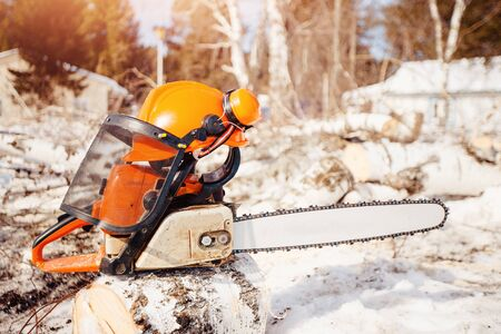 Chainsaw and protective helmet with headphones lie on sawn wood on sawmill.