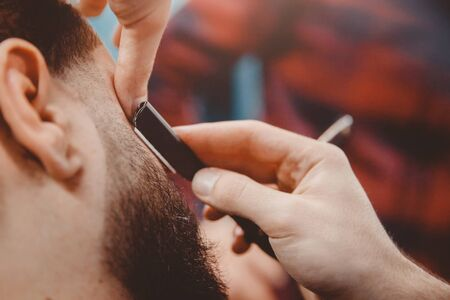 Man with beard client in barbershop hairdresser on shaving with dangerous razor. Stock Photo