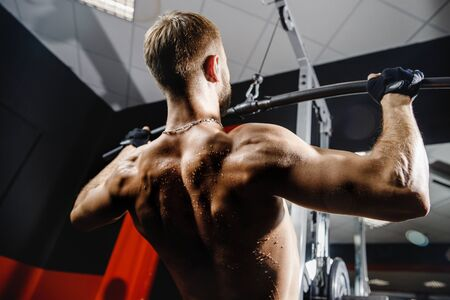Man muscles are back. Close-up of an athlete makes traction on muscles of delta, shoulders, biceps
