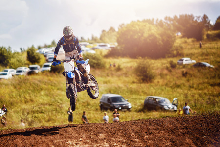 Racer on dirtbike motorcycle jumps and takes off over the track, in background opponent is catching up. Concept primacy, rivalry, competition, extreme Фото со стока