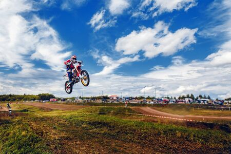 Racer on dirtbike motorcycle jumps and takes off over the track, in background opponent is catching up. Concept primacy, rivalry, competition, extreme Stock Photo