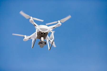 Drone quad copter on radio control fly against background of an isolated blue sky.