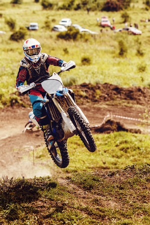 Racer on dirtbike motorcycle jumps and takes off over track, in background opponent is catching up. Concept primacy, rivalry, competition, extreme