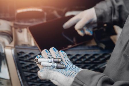 Primer plano de mecánico de automóviles con vela eléctrica para coche. Diagnóstico de concepto con computadora.