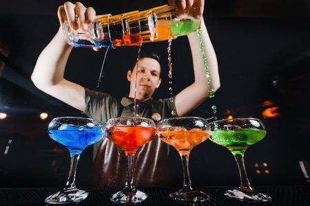 Barman mixes cocktail show with colorful alcoholic cocktails at bar counter. Standard-Bild