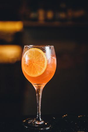 Close-up of barman mixes cocktail with ice orange, whiskey, liquor.