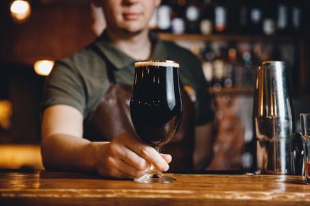 Barman serves glass of dark cold beer at bar counter.