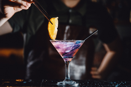 Barman prepares cocktail with orange and martini purple color on bar with alcohol. Uses tongs for decoration. Dark background. Stock Photo