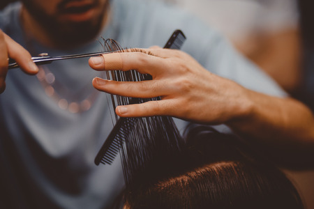 Barbershop. Close-up of man haircut, master does the hair styling in barber shop Stockfoto