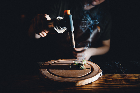 Barman is preparing a cocktail with smoke, herbs using burner. Dark background. Stock Photo