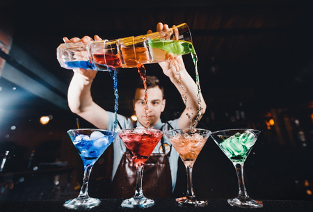 Barman mixes cocktail show with colorful alcoholic cocktails at bar counter. Stock Photo