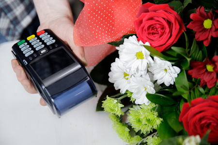 Credit card payment in salon florist shop. Man holding terminal bank.