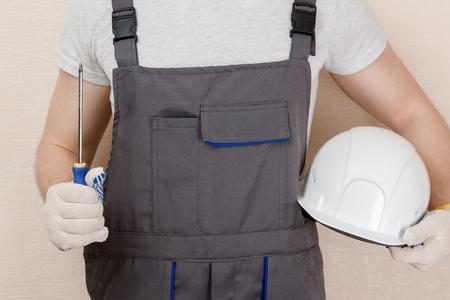 Man in uniform of delivery suit, loader, holding screwdriver Foto de archivo