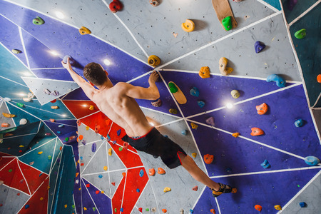 climber on sports climbing wall up, muscular body, rear view