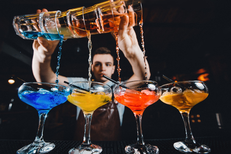 Barman mixes cocktail show with colorful alcoholic cocktails at bar counter. Imagens