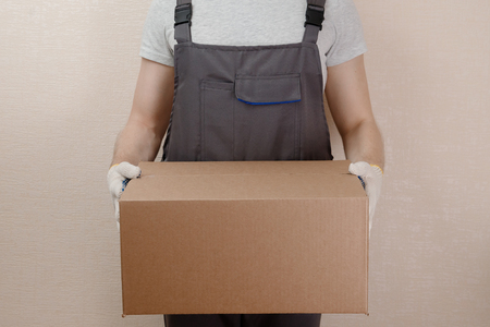 Man in uniform of delivery suit, loader, in hands of cardboard box for things