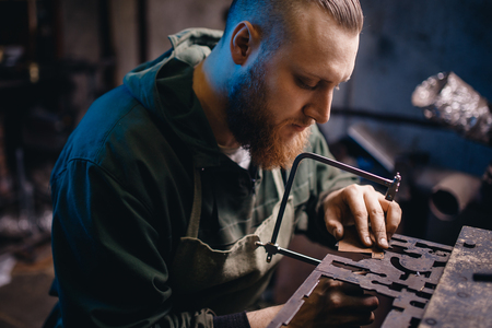 Modern worker performs work with metal, cuts out a detail, jeweler. Zdjęcie Seryjne