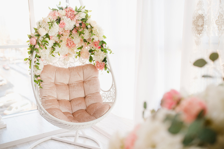 Chair on chains levitates in white room. Decorated with flowers