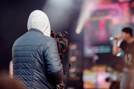 Videographer stands with his back in frame, takes recording concert on camera, an event. Stock Photo