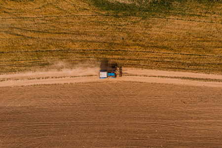 Tractor on farm field is carried by hay, view from above, aerial photography