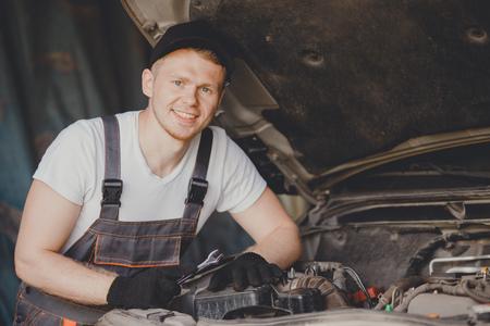 Mechanic working in auto repair service car
