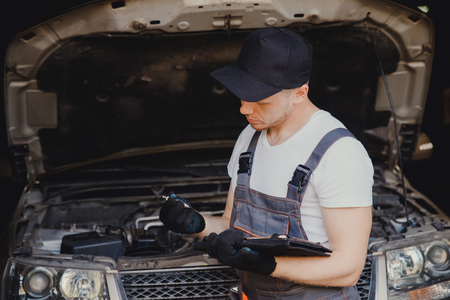 Professional car mechanic using plug spark in auto repair service.