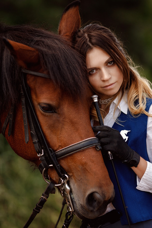 Young woman rider hugging with brown horse, eyes closed. Concept friends