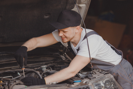 Car mechanic working diagnostic equipment at automotive service. Cleaning air filter. Stock Photo