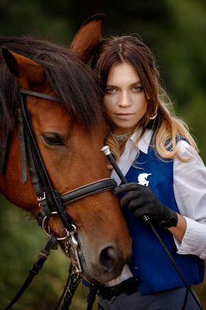 Face of young woman rider equestrian and brown horse touch each other, concept friends. Stock Photo