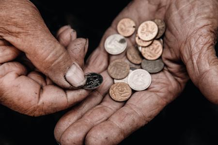 Concepto de pobreza en Rusia, pueblo de la CEI, URSS. Manos viejas sostienen rublo