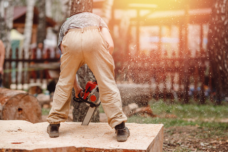 Close-up of woodcutter lumberjack is man chainsaw tree. Stock Photo - 106838618